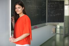 在黑板的俏丽,年轻大学生文字 免版税库存图片