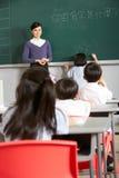 在黑板的女性学生文字在学校 免版税库存图片