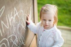 在黑板的小女孩图画 获得小孩的女孩乐趣户外,举行白垩和画 免版税库存照片