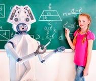 在黑板的小学生和ai机器人机器人文字在教室 免版税库存照片