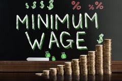 在黑板的最低工资 免版税库存图片