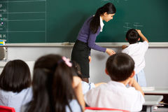 在黑板的男性学生文字在中国学校 免版税图库摄影