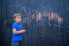 在黑板的美丽的男孩图画 图库摄影