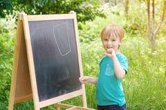 在黑板的逗人喜爱的小男孩图画有白垩的,室外在夏天晴天 回到概念学校 库存照片