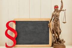 在黑板背景旁边的Justitia当法律概念 图库摄影