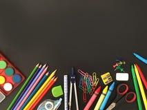 在黑板背景的学校用品 免版税图库摄影