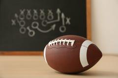 在黑板附近的橄榄球球有足球比赛计划的 库存图片