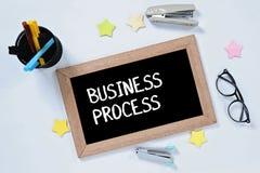 在黑板顶视图的商业运作词有玻璃、笔盒、订书机和标志的 免版税库存照片