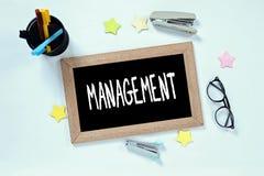 在黑板顶视图的管理词有玻璃、笔盒、订书机和标志的 免版税库存图片