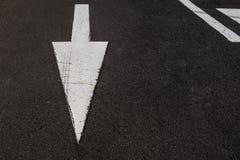 在黑柏油路背景的白色箭头, 库存图片
