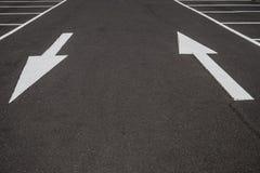 在黑柏油路背景的白色箭头, 免版税库存照片