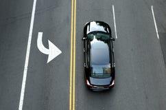 在黑汽车的顶视图在路 黄色双重实线 免版税库存图片