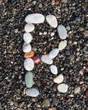 在黑沙子放置的字母表上写字 r 库存图片