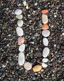 在黑沙子放置的字母表上写字 U 免版税库存图片