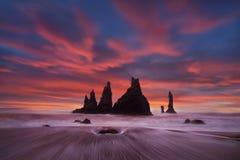 在黑沙滩的冰岛Reynisdrangar峭壁在维克旋转手指 与大西洋的不高兴的风景 图库摄影