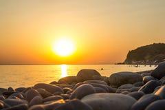 在黑海和橙色天空的美好的燃烧的日落风景在它上作为背景 库存照片