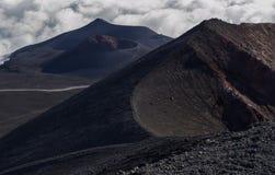 在黑熔岩的一条道路在绝种火山口之间在云彩之间的Etna火山顶部 库存照片