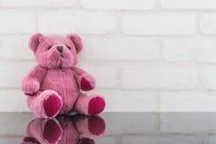 在黑玻璃桌和白色砖墙上的特写镜头逗人喜爱的桃红色熊玩偶构造了与拷贝空间的背景 免版税库存图片
