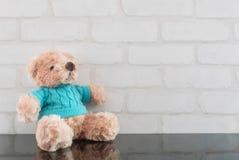 在黑玻璃桌和白色砖墙上的特写镜头逗人喜爱的棕熊玩偶构造了与拷贝空间的背景 库存图片