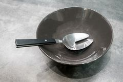 在黑瓷碗的金属银色叉子 免版税图库摄影