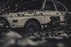 在黑白场面的老被击毁的汽车 被放弃的生锈的汽车在bokeh背景的森林里 腐朽的和生锈的被击毁的摒弃 免版税库存照片