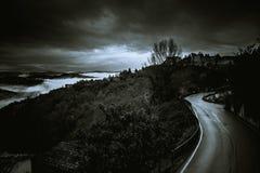 在黑白的云彩的黑暗和危险路- 免版税库存图片