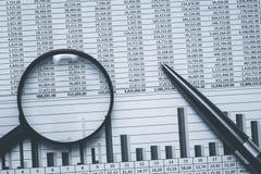 在黑白的财政储蓄银行业务会计报表数据 与放大镜和bla的概念性单色照片 免版税库存图片