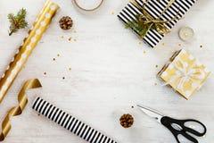 在黑白镶边包裹的礼物盒和goden被加点的纸与,杉木、锥体、蜡烛和包装用材料在白色w 免版税库存照片