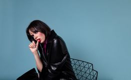 在黑皮夹克的年轻短的黑色头发模型坐椅子 库存照片