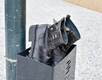 在黑皮革做的一个对使用的黑起动放弃在黑容器 起动和容器在一个岗位在街道的边路 免版税库存图片