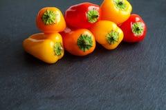在黑石头的鲜美甜椒胡椒 明亮的红色橙黄菜,拷贝空间背景 图库摄影