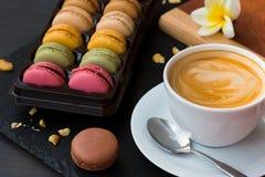 在黑石背景的法国macarons 与一个杯子的早晨好您的鲜美咖啡和喜爱预定 免版税库存图片