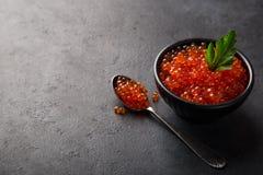 在黑碗的可口红色鱼子酱 免版税库存照片