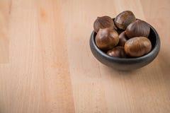 在黑碗的欧洲栗木在木背景 免版税库存图片