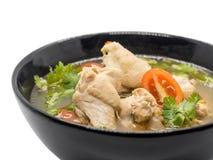 在黑碗的热和辣鸡汤在白色背景 免版税库存照片