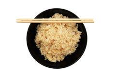在黑碗的蒸的健康未磨光的糙米和chopstic 库存图片