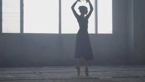 在黑礼服的优美的芭蕾舞女演员跳舞在一个大窗口前面的演播室 年轻美丽的跳芭蕾舞者 股票视频