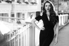 在黑礼服的华美的女性模型有保险开关的担负 库存照片
