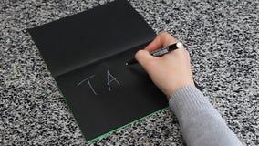 在黑纸放置的桌上的女性手拼写税 影视素材