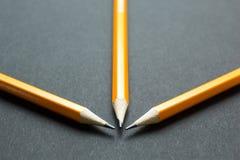 在黑纸的三支黄色铅笔 免版税库存照片