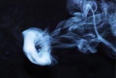 在黑织品背景的白色烟圆环 烟延长了背景 Vaping文化,没有香烟的生活 库存照片
