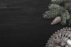 在黑背景、一棵杉树与锥体和装饰对象 寒假消息的空间  免版税库存照片
