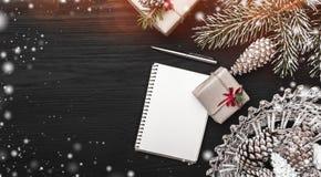 在黑背景、一棵杉树与锥体和装饰对象 礼物和笔记本或者圣诞节消息 库存照片