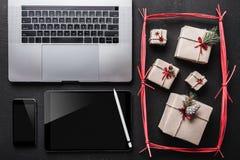在黑背景、许多礼物和技术 在片剂屏幕上您能为您亲人写消息 免版税库存照片