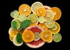 在黑背景关闭隔绝的切的柑橘水果,顶视图 水多的成熟桔子,蜜桔,葡萄柚,石灰 免版税库存图片