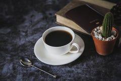 在黑背景和仙人掌的无奶咖啡安置的一个加奶咖啡杯子 图库摄影