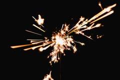 在黑背景在晚上,假日铈的灼烧的闪烁发光物疾风 免版税库存图片