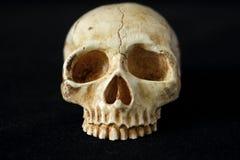 在黑背景的一块邪恶的人的头骨 免版税库存图片