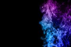 在黑背景的五颜六色的蓝色桃红色烟 库存照片