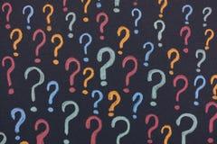在黑背景的五颜六色的问号 免版税库存照片